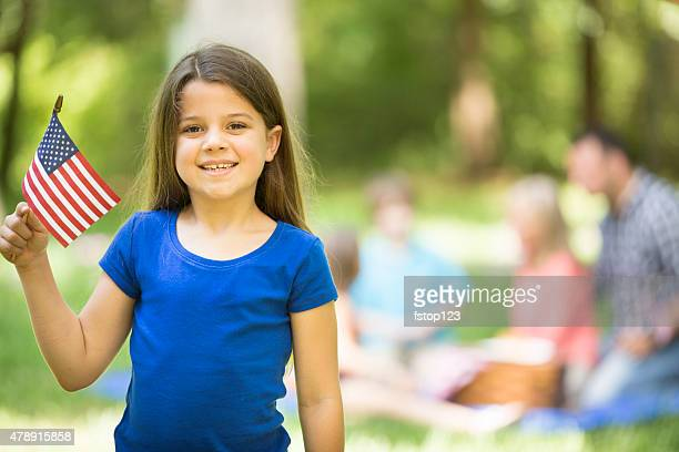 Child holds American flag outdoors, summer family picnic. July 4th.