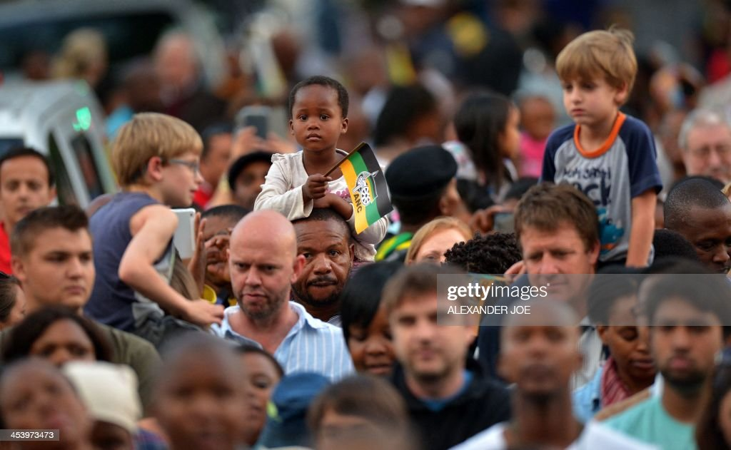 A child holds an ANC flag as people pray at an ANC party meeting outside the home of South African president Nelson Mandela in Johannesburg on December 6, 2013 where he died the day before. Mandela, the revered icon of the anti-apartheid struggle in South Africa and one of the towering political figures of the 20th century, has died aged 95. Mandela, who was elected South Africa's first black president after spending nearly three decades in prison, had been receiving treatment for a lung infection at his Johannesburg home since September, after three months in hospital in a critical state.