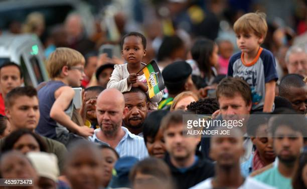 A child holds an ANC flag as people pray at an ANC party meeting outside the home of South African president Nelson Mandela in Johannesburg on...