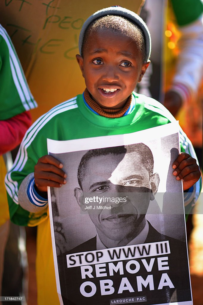 A child holds an anti-war poster featuring a likeness of <a gi-track='captionPersonalityLinkClicked' href=/galleries/search?phrase=Barack+Obama&family=editorial&specificpeople=203260 ng-click='$event.stopPropagation()'>Barack Obama</a> amongst protesters gathered outside Johannesburg University in Soweto in advance of US President Obama'smeeting with students later today on June 29, 2013 in Johannesburg, South Africa. This is Obama's first official visit to South Africa, and is holding bilaterial meetings with President Jacob Zuma, and also meeting with students in Soweto Township. During his tour the president will also visit Robben Island, where former President Nelson Mandela spent some of his 27 years in prison for fighting against apartheid.