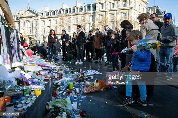 A child holds flowers as the streets of Paris are quiet surrounding Place de la Republique as France observes three days of national mourning for the...
