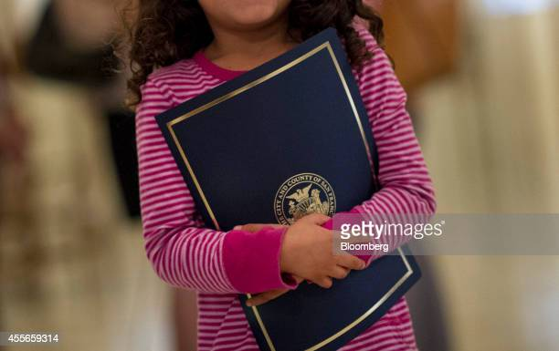 A child holds her Certificate of Honor after attending a San Francisco Board of Supervisors meeting in San Francisco California US on Tuesday Sept 16...