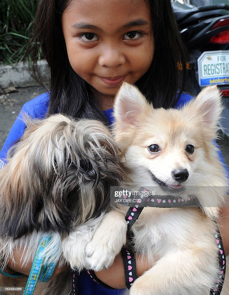 A child holds her pet dogs after a Roman Catholic priest blessed animals with holy water on the first Sunday of October after a mass for World Animal Day in Manila on October 6, 2013. People around the globe celebrated World Animal Day, which began as a holiday in Florence, Italy, in 1931 at a convention of ecologists, to highlight the plight of endangered species. AFP PHOTO / Jay DIRECTO