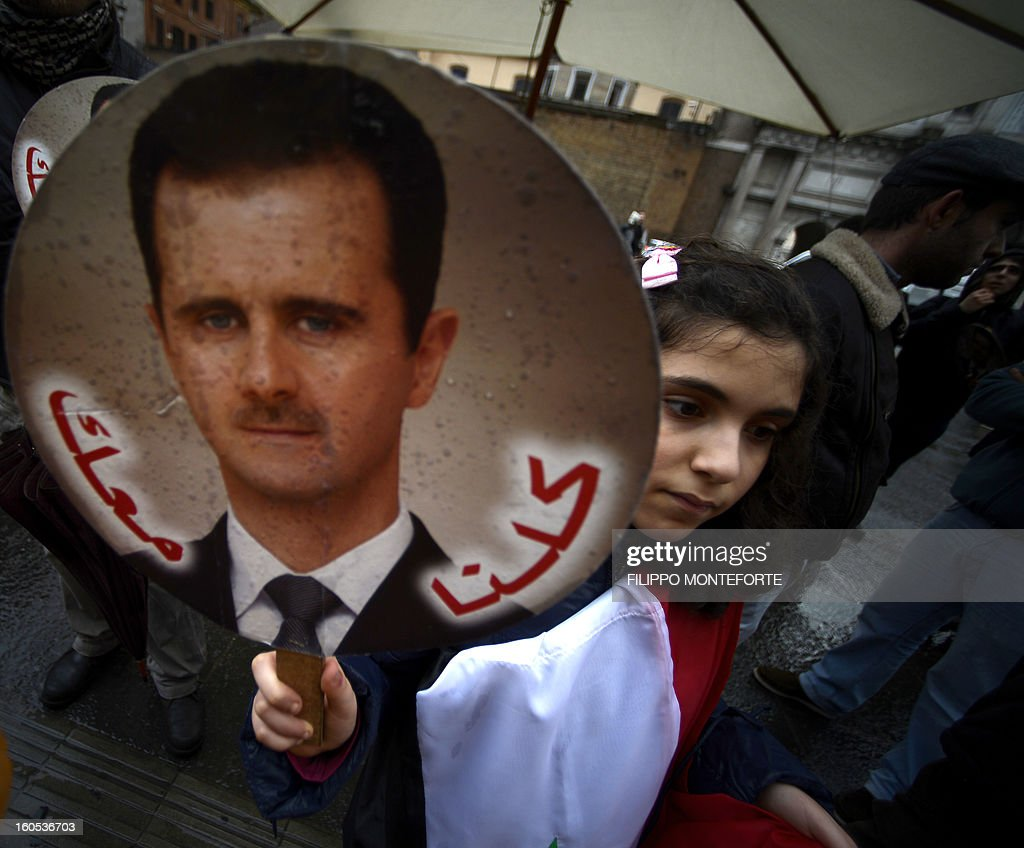 A child holds portraits of Bachar al-Assad during a demonstration of some 30 people in support of Syria's president in downtown Rome on February 2, 2013 AFP PHOTO/ Filippo MONTEFORTE