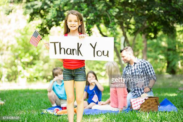 Child holds 'Thank You' sign with American flag. Memorial Day.
