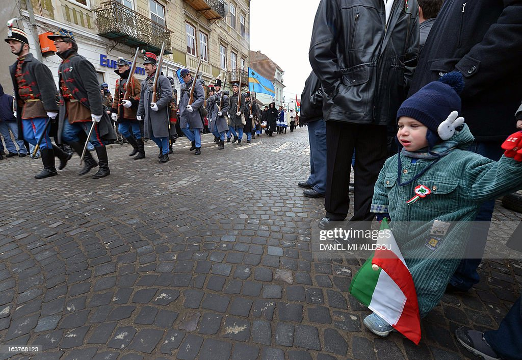 A child holds the hungarian flag as he watches a parade on Hungary's National Day in Targu Secuiesc (250km north of Bucharest) on March 15, 2013. Thousands of ethnic Hungarians from the central Transylvanian region of Romania gather in a celebration in Targu Secuiesc to mark the 1848 Hungarian Revolution.