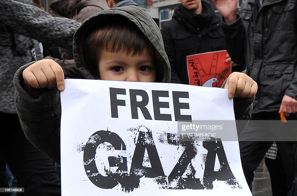 A child holds up a poster during a march on November 20, 2012, through the center of Sarajevo in support of Palestinian people following the latest Israeli attacks in Gaza. Israel's air force dropped leaflets across Gaza City on Tuesday urging people to evacuate their homes 'immediately' amid fears the military was poised to launch a ground operation. The violence comes as Israel heads towards a general election in January, raising the spectre of a broader Israeli military campaign along the lines of its devastating 22-day Operation Cast Lead launched at the end of December 2008. AFP PHOTO ELVIS BARUKCIC
