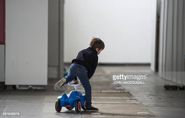 A child housed in a temporary shelter for refugees located in one of the halls of Berlin's trade fair ground rides a toy car in Berlin October 7 2015...