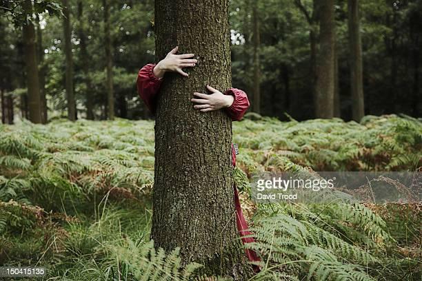 Child hugging tree.