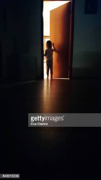 Child in a dark hallway, opening a door into the light