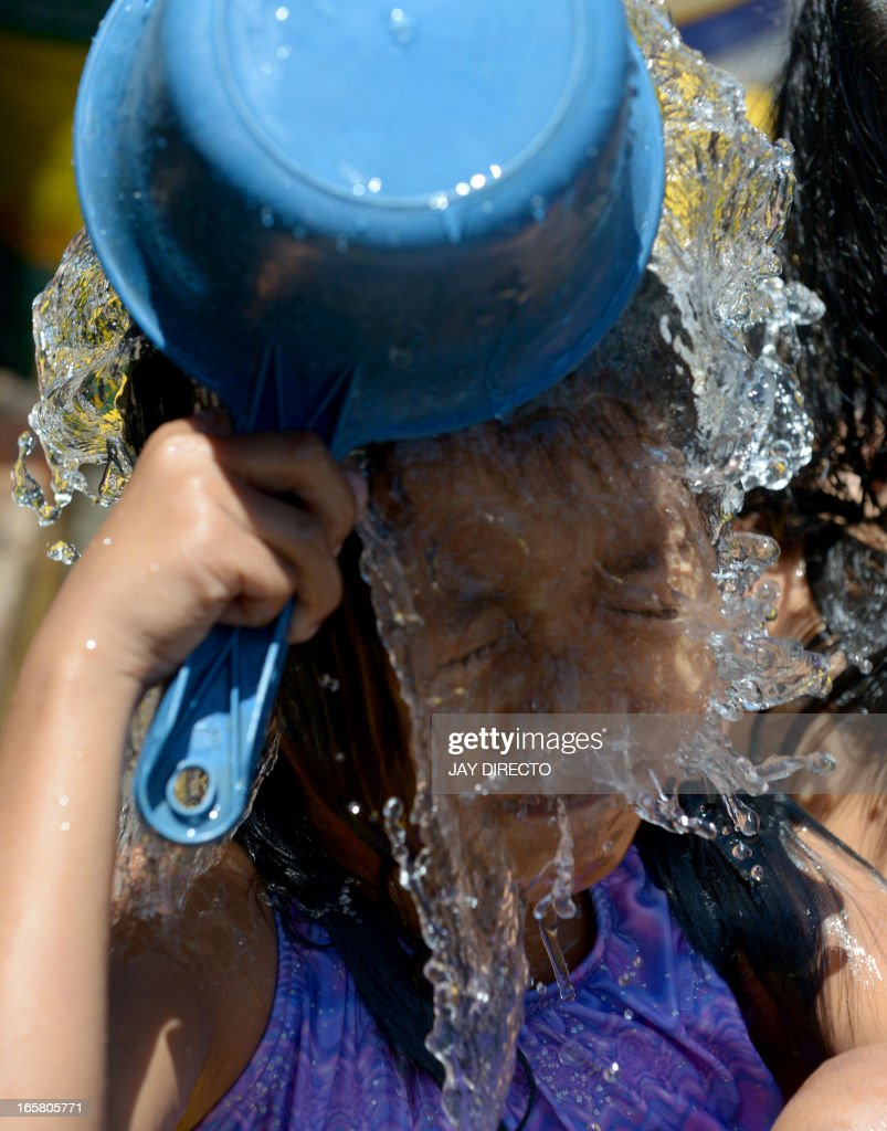 A child in a slum area in Manila cools off with water to get relief from the scorching heat on April 6, 2013. The Philippines has been experiencing the hottest days of the year with temperatures of 35 degrees Celsius (95 Fahrenheit) recorded in parts of the city. The Health Department has warned that people could suffer heat stroke or sun burn, but also warned against infectious disease if they bathe in dirty water to escape the high temperatures. AFP PHOTO / Jay DIRECTO