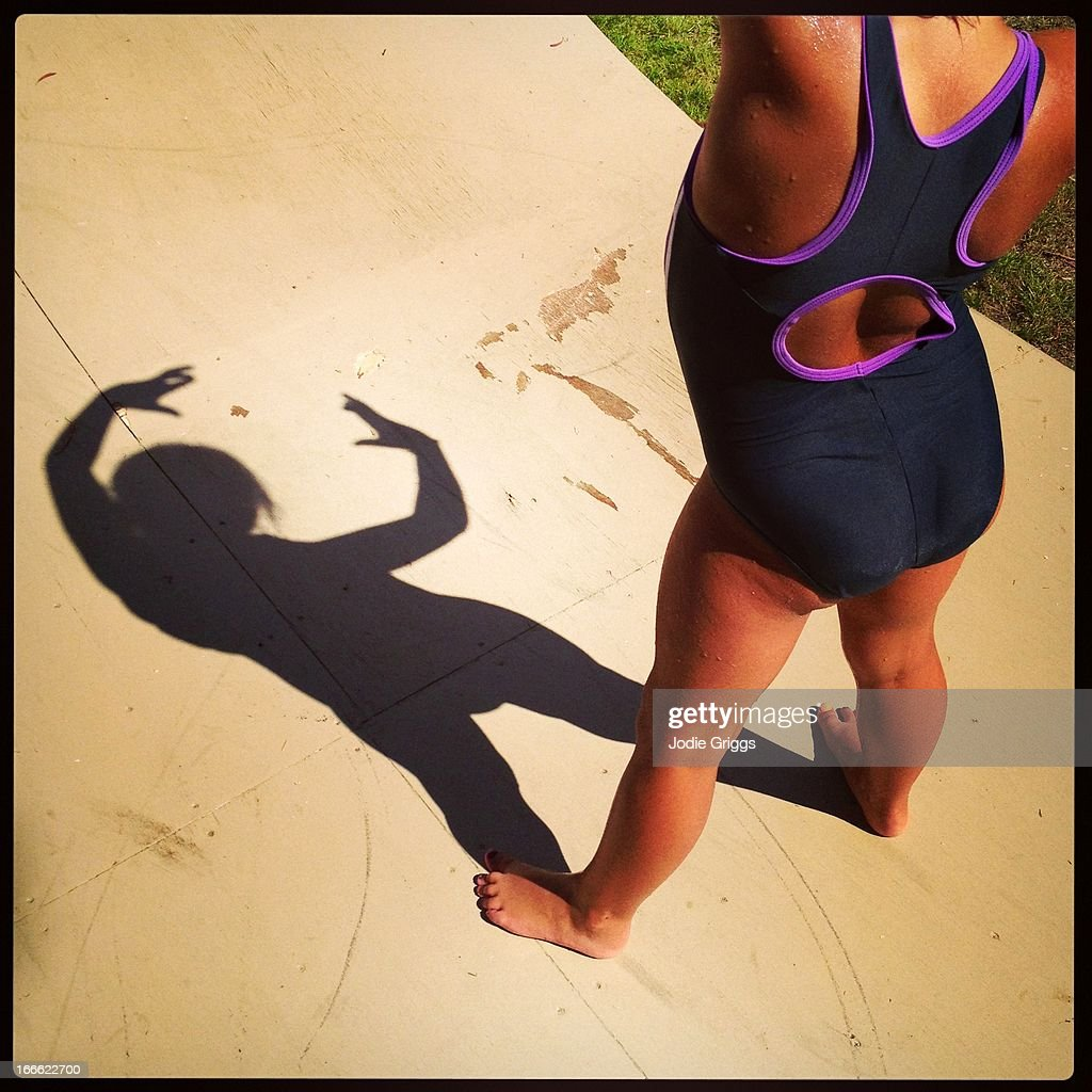 Child in bathing suit making shadows on the ground : Stock Photo