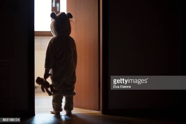 Child in bear costume, standing in a darkened doorway, looking through to the light