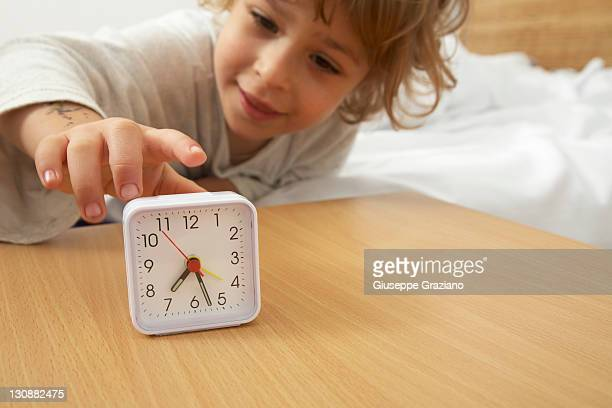 Child in bed with alarm clock