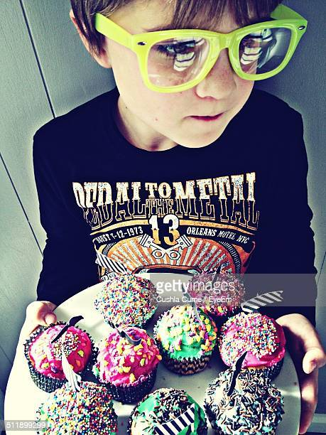 Child in big green glasses holding cupcakes