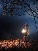 Child in costume in dark forest scene.