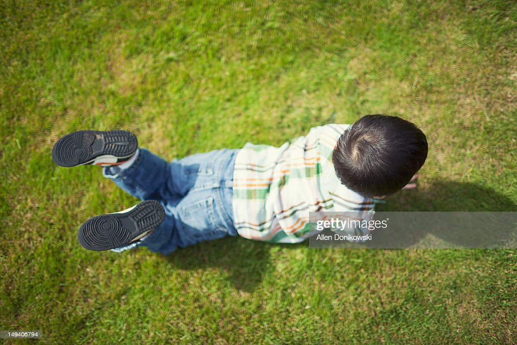 Child in grass laying with his shadow : Stock Photo