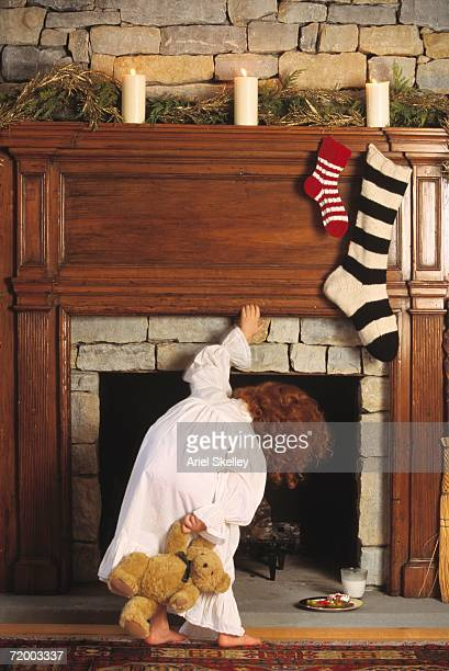 Child in pajamas looking up chimney with stockings hanging on it