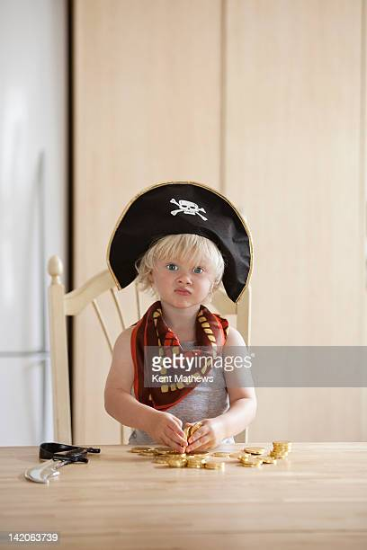 child in pirate outfit with gold coins