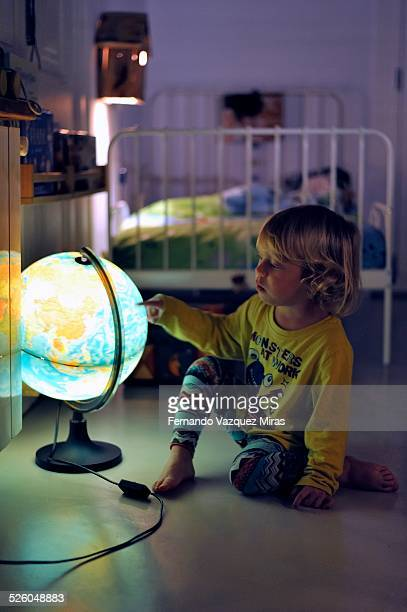 Child in pyjamas with a light-up globe