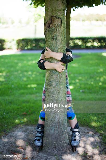 child in skating outfit on skates holding tree
