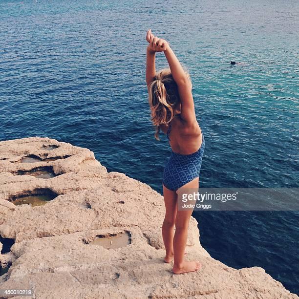 Child in swimsuit standing on rocks beside ocean