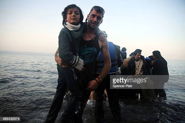 A child is assisted as a group of migrants land on a beach with a raft from Turkey onto the island of Lesbos on October 20 2015 in Sikaminias Greece...