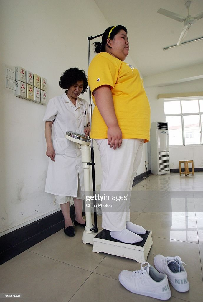 A child is being weighed at a base of the Aimin Slimming Centre on July 10, 2007 in Wuhan of Hubei Province, China. Doctors in the center have combined acupuncture, exercise and diet to help about 110 obese teenagers from 9 to 20 years old lose weight during one month. An official from the Ministry of Health revealed that more than 200 million Chinese people are overweight.