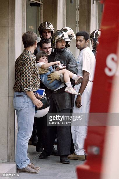 A child is carried by a fireman after the explosion of a gas bottle packed with screws and hidden in a rubbish bin on August 17 1995 outside a subway...