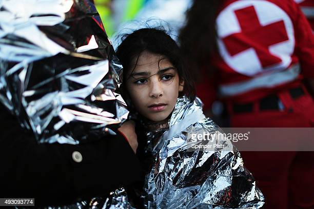 A child is comforted after arriving on a raft moments before from Turkey onto the island of Lesbos on October 17 2015 in Sikaminias Greece Dozens of...