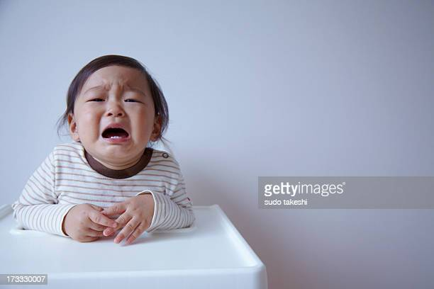 Child is crying sitting on baby chair.