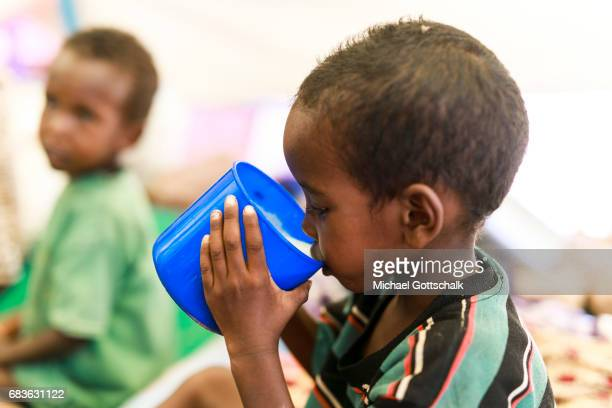 A child is drinking milk made of milk powder at the Unicef feeding in a village in the Somali region of Ethiopia where Pastorale have settled because...