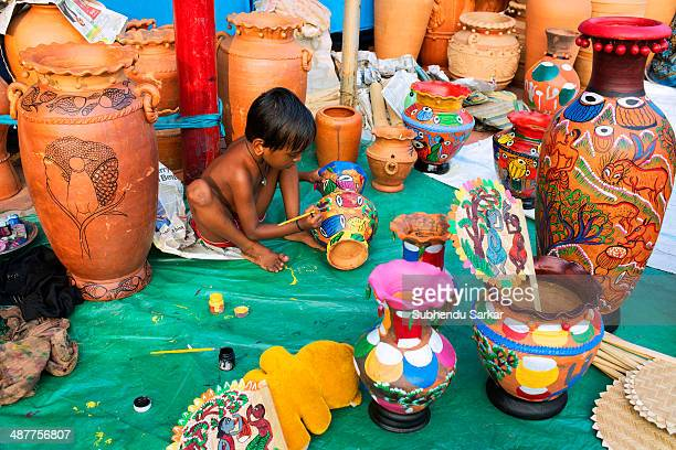 A child is engaged in colouring earthen vessel Pottery is quite famous in West Bengal The smallscale industry of pottery is carried on mainly in the...