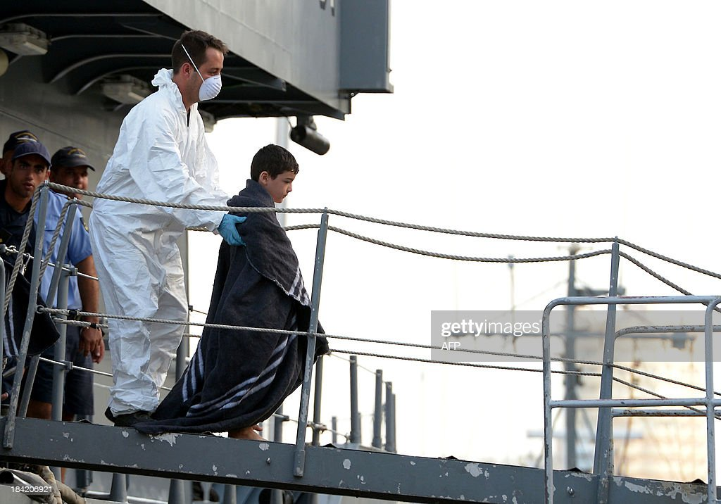 A child is escorted by a rescue worker after being rescued by a patrol boat of the Armed forces of Malta at Hay Wharf in Valletta on October 12, 2013, a day after a boat carrying migrants sank. More than 140 survivors, plucked from the sea after their overloaded boat sank in the latest deadly migrant tragedy to hit the Mediterranean, arrived in Malta. The sinking killed more than 30, most of them women and children, when the boat packed with people desperate to reach European shores went down off Malta near the Italian island of Lampedusa, according to officials.