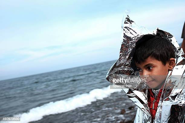 A child is kept warm after arriving from Turkey on a raft onto the island of Lesbos on October 16 2015 in Sikaminias Greece Dozens of rafts and boats...