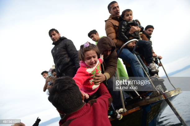 A child is lifted off as migrants and refugees disembark helped by life guards on the Greek island of Lesbos after crossing the Aegean Sea from...