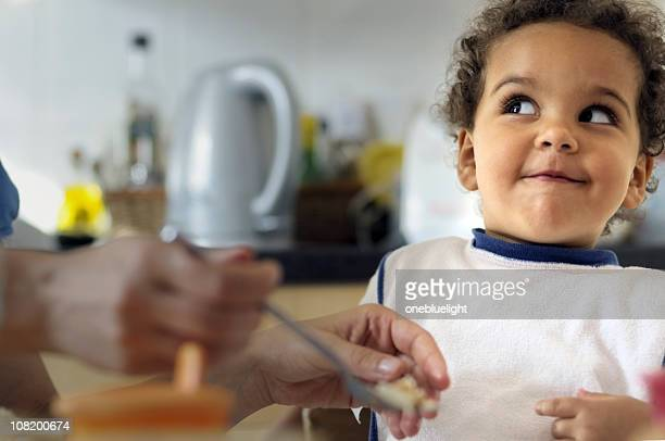 Drôle enfant est de faire Face en déjeunant