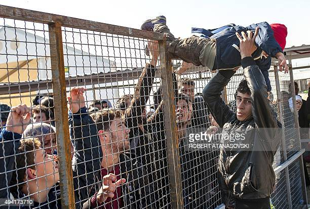 A child is passed over a fence as migrants and refugees prepare to board a train heading to Serbia from the MacedonianGreek border near Gevgelija on...