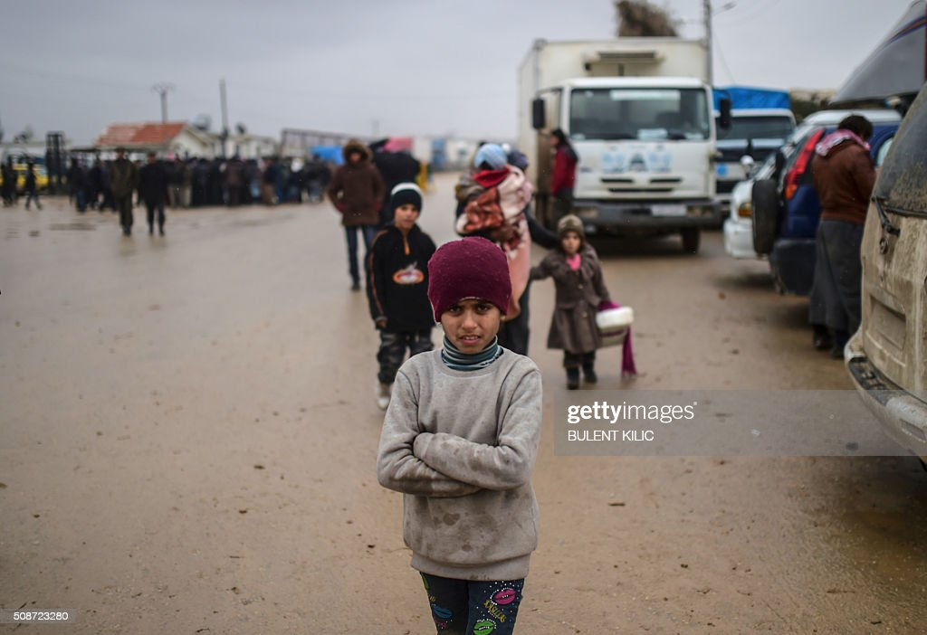 A child is pictured as aefugees arrive at the Turkish border crossing gate while Syrians fleeing the northern embattled city of Aleppo wait on February 6, 2016 in Bab-Al Salam, near the city of Azaz, northern Syria. Thousands of Syrians were braving cold and rain at the Turkish border Saturday after fleeing a Russian-backed regime offensive on Aleppo that threatens a fresh humanitarian disaster in the country's second city. Around 40,000 civilians have fled their homes over the regime offensive, according to the Syrian Observatory for Human Rights monitor. / AFP / BULENT KILIC