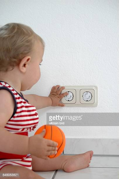 child is playing with a childproof socket
