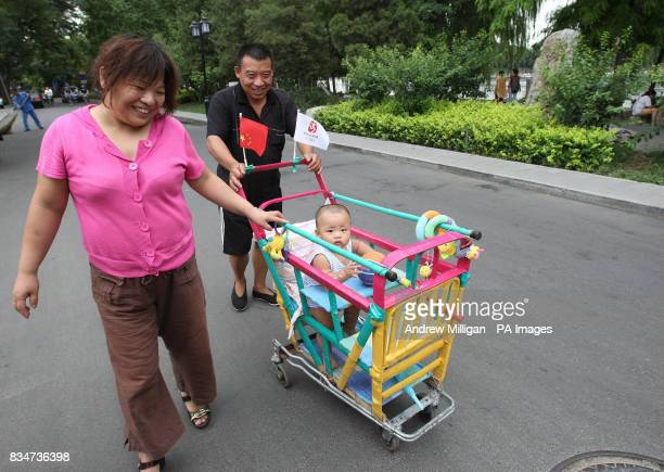 A child is pushed down a road in a trolley near Hou Hai lake in Old Beijing China
