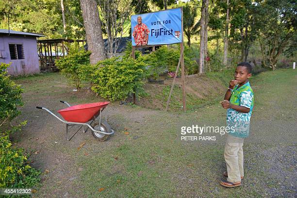 A child is seen next to an election poster of Fiji's military strongman Voreqe Bainimarama outside their home in a village near Sigatoka 60...