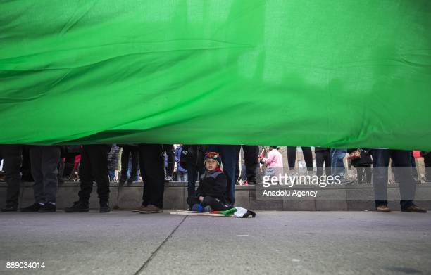 A child is seen under a giant Palestinian flag as protesters walk across University Avenue in front of the US consulate during a demonstration...