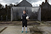 child is stood holding a football under one arm.