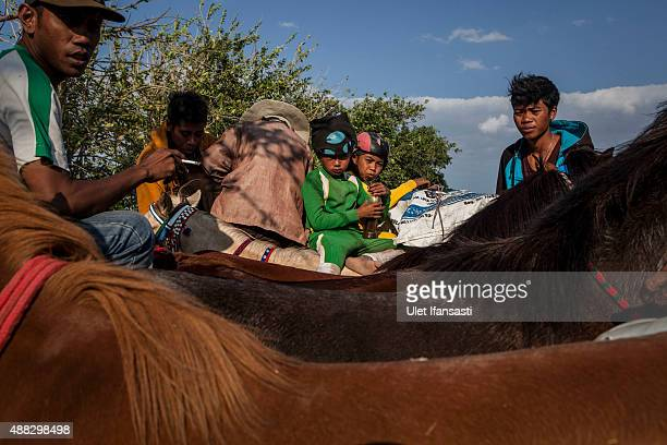 Child jockeys sit on the back of truck with their horses after the race during the traditional horse races as part of Moyo festival on September 14...