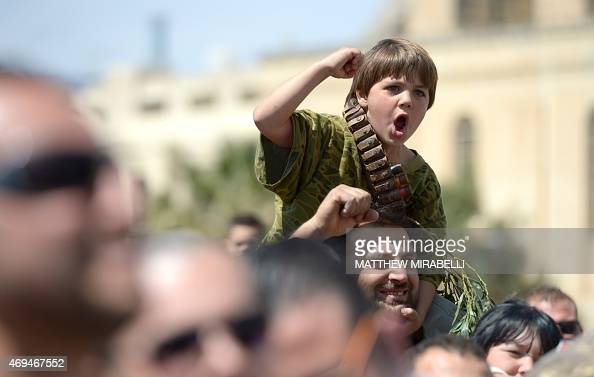 A child jubilates as Maltese hunters gather to celebrate the result of the referendum on hunting on April 12 2015 in Qormi Malta has voted in a...