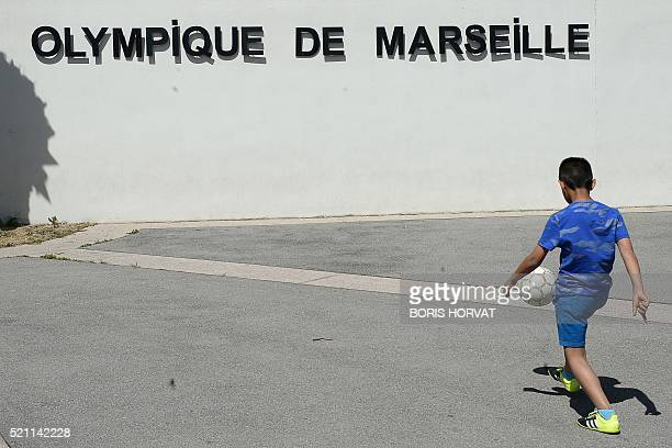 A child juggles with his ball outside the Olympique de Marseille training camp in Marseille on April 14 2016 The owner of struggling French giants...