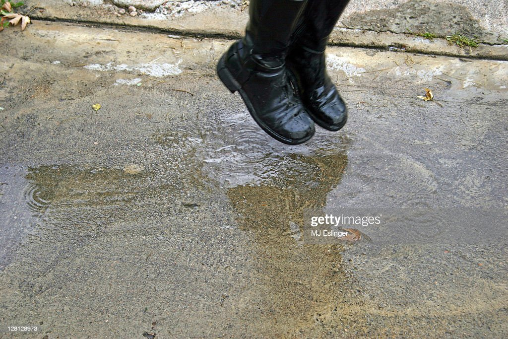 A child jumping and about to land in a puddle : Stock Photo