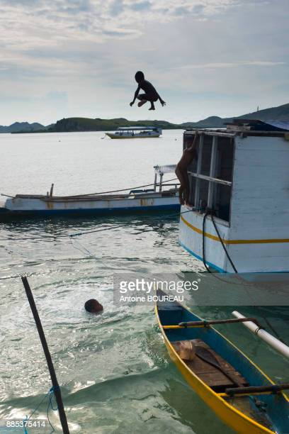 Child jumping from a boat moored at the port of Pulau Messah, Flores, Indonesia