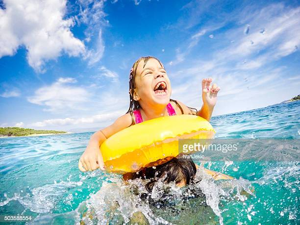 Child jumping from father's arms in sea